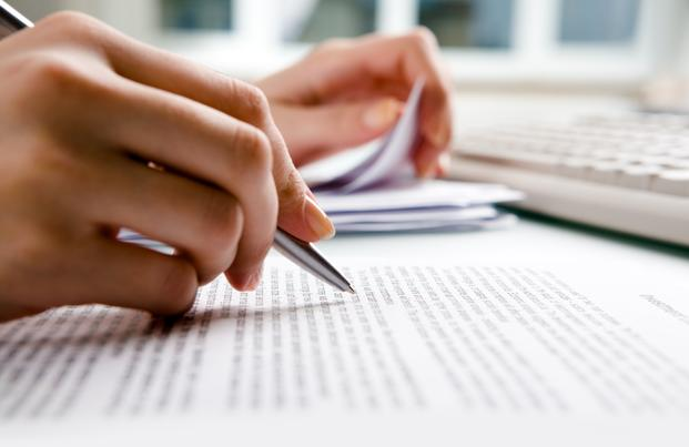 Person with pen on hand underlining words on paper