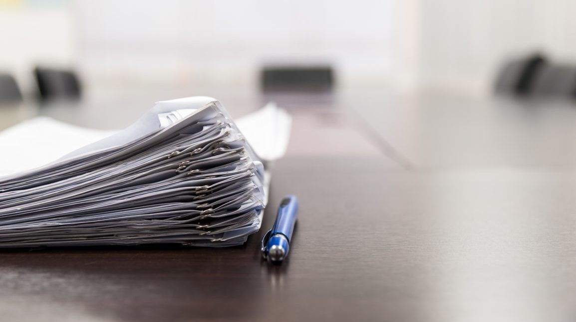 Stack of papers on desk with pen on the side