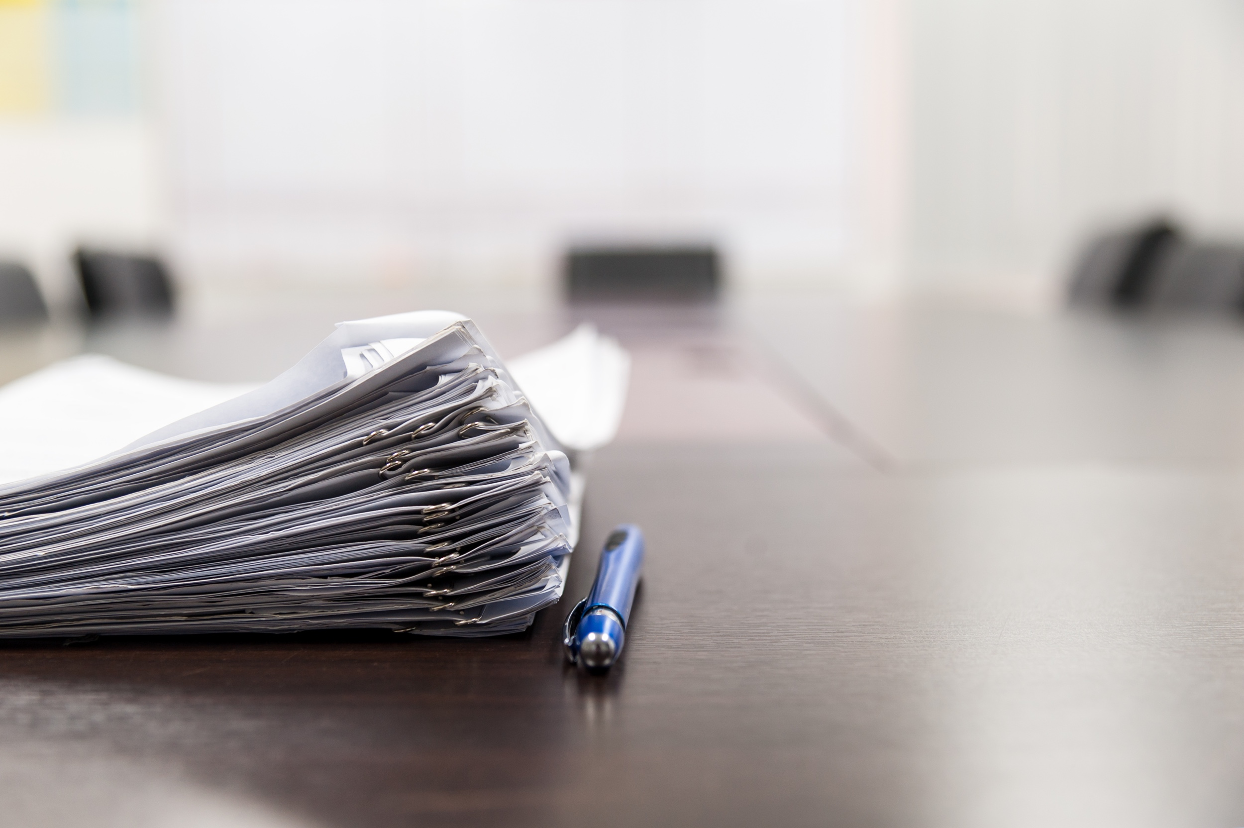 Pile of documents and blue pen on the meeting table with blurred background. Conceptual job interview.; Shutterstock ID 608600555; PO: Mariela; Job: StreetEasy Blog