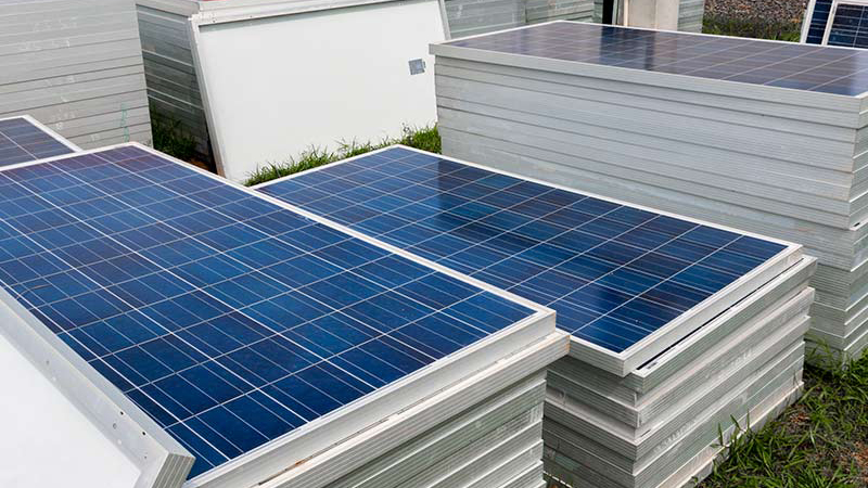 Solar Panels Stacked On Top Of Each Other On The Ground