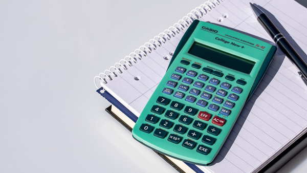 teal calculator on top of a notebook with pen on the side