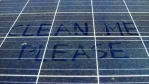 clean me please written with the dust on a solar panel