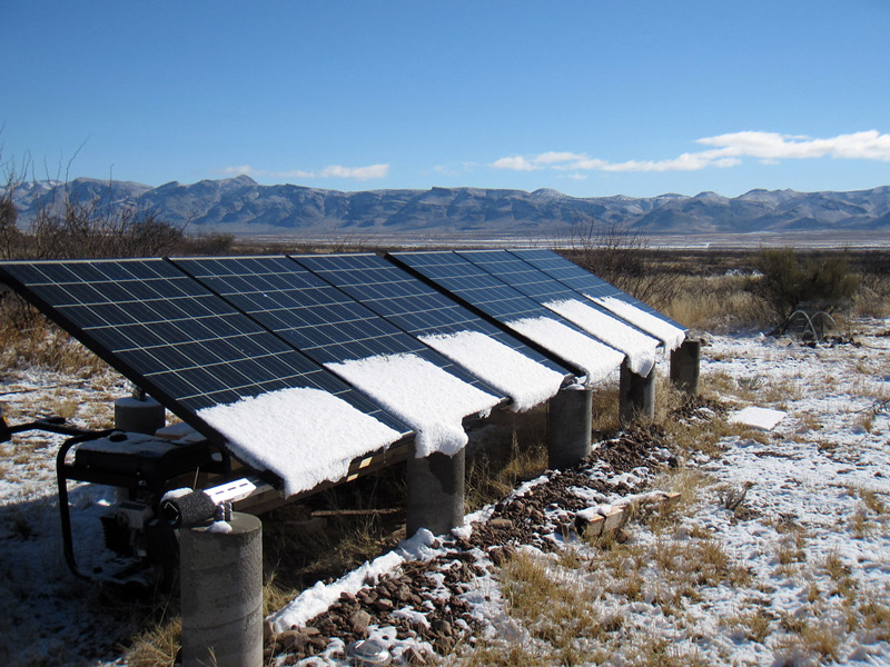 Solar panels with snow on them with mountains in the background