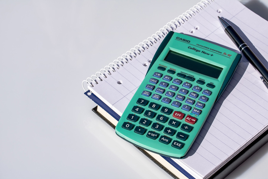 Teal calculator on top of a notebook with a pen on the side