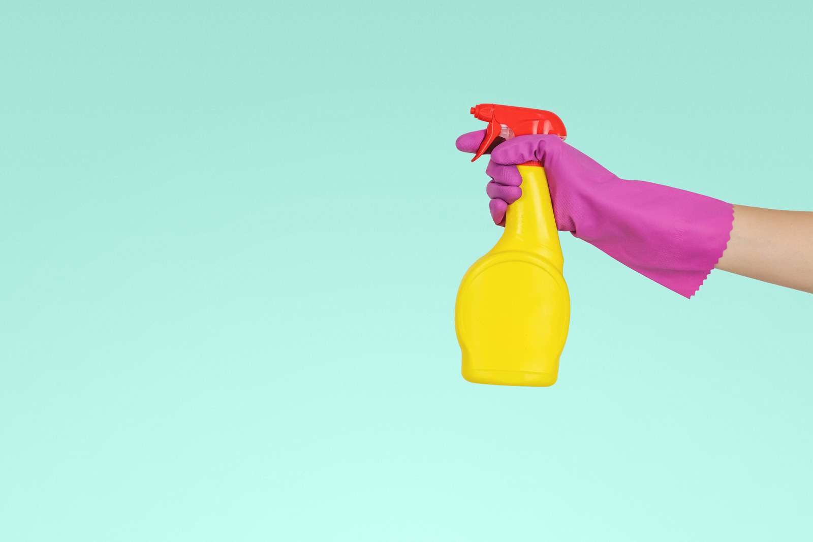 A person with a pick glove holding a yellow spray bottle with orange on top