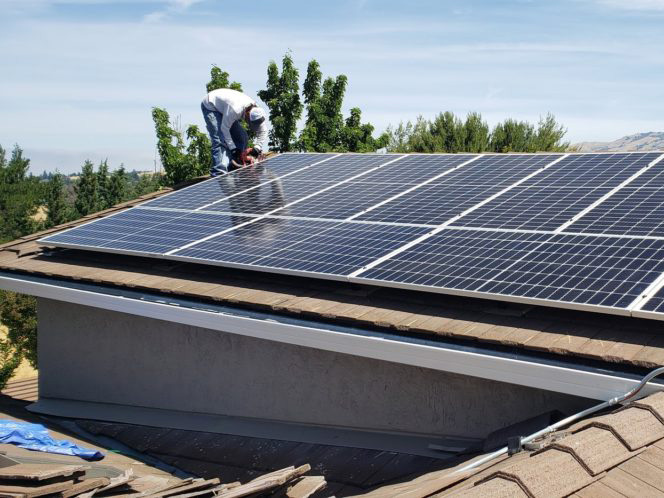 A person installing solar panels on a roof
