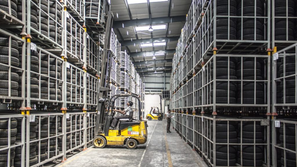 Forklift lifting heavy items in warehouse