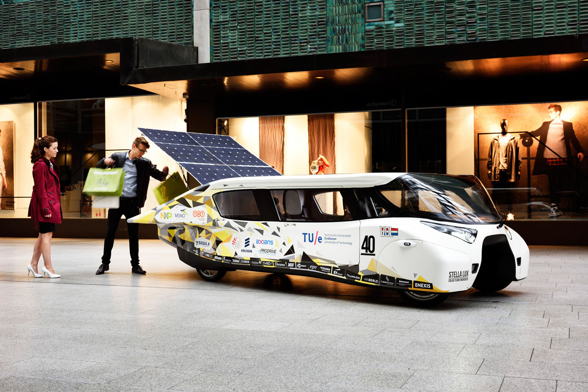 A man loading shopping bags into the back of a mostly white solar car while a woman watches