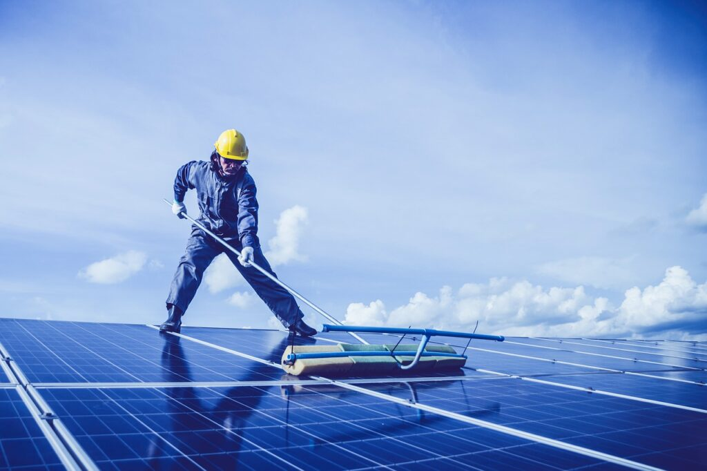 man cleaning dirty solar panels